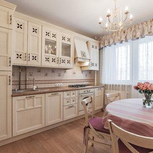Свежая идея для дизайна: линейная кухня в стиле шебби-шик с накладной раковиной, фасадами с утопленной филенкой, бежевыми фасадами, бежевым фартуком, белой техникой и коричневым полом без острова - отличное фото интерьера