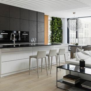 На фото: кухни-гостиные в современном стиле с монолитной раковиной, черными фасадами, черной техникой, островом, плоскими фасадами, светлым паркетным полом и черной столешницей