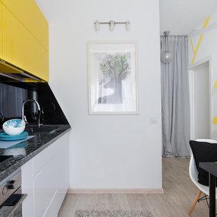 サンクトペテルブルクの小さいおしゃれなキッチン (ドロップインシンク、フラットパネル扉のキャビネット、黄色いキャビネット、人工大理石カウンター、黒いキッチンパネル、ガラス板のキッチンパネル、シルバーの調理設備、ラミネートの床、アイランドなし、ベージュの床、黒いキッチンカウンター) の写真