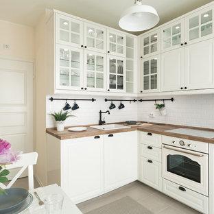 Неиссякаемый источник вдохновения для домашнего уюта: угловая кухня в стиле современная классика с обеденным столом, накладной раковиной, стеклянными фасадами, белыми фасадами, деревянной столешницей, белым фартуком, фартуком из плитки кабанчик, белой техникой и серым полом без острова