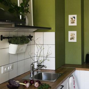 Стильный дизайн: угловая кухня среднего размера в скандинавском стиле с обеденным столом, белыми фасадами, деревянной столешницей, белым фартуком, фартуком из керамической плитки, черной техникой, коричневой столешницей, накладной раковиной и фасадами с утопленной филенкой без острова - последний тренд