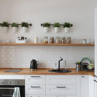 Пример оригинального дизайна: угловая, отдельная кухня в стиле современная классика с накладной раковиной, фасадами в стиле шейкер, белыми фасадами, деревянной столешницей, белым фартуком, фартуком из плитки кабанчик, коричневой столешницей и техникой из нержавеющей стали без острова