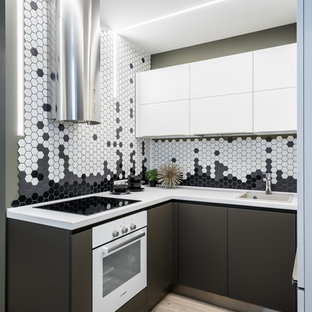 Неиссякаемый источник вдохновения для домашнего уюта: маленькая п-образная кухня в современном стиле с накладной раковиной, плоскими фасадами, разноцветным фартуком, белой техникой, бежевым полом, серыми фасадами, фартуком из плитки мозаики и светлым паркетным полом без острова
