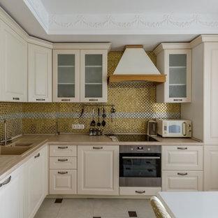 Идея дизайна: угловая кухня в классическом стиле с накладной раковиной, фасадами с выступающей филенкой, бежевыми фасадами, желтым фартуком, фартуком из плитки мозаики, техникой из нержавеющей стали, серым полом и бежевой столешницей без острова