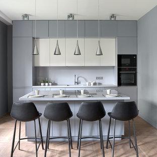 На фото: параллельные кухни в современном стиле с плоскими фасадами, серыми фасадами, островом, коричневым полом и серой столешницей