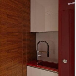 Modelo de cocina lineal, contemporánea, pequeña, con fregadero integrado, armarios con paneles lisos, encimera de cuarcita, salpicadero blanco, salpicadero de vidrio templado, suelo de mármol, suelo blanco y encimeras rojas