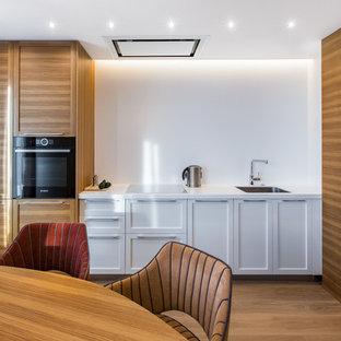 Пример оригинального дизайна: прямая кухня в современном стиле с врезной раковиной, белыми фасадами, белым фартуком, черной техникой, паркетным полом среднего тона, коричневым полом, белой столешницей, обеденным столом и фасадами в стиле шейкер без острова