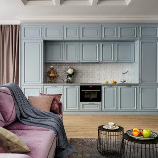 Новый формат декора квартиры: линейная кухня-гостиная в стиле современная классика с фасадами с выступающей филенкой, белым фартуком, фартуком из плитки кабанчик, черной техникой, паркетным полом среднего тона и коричневым полом без острова