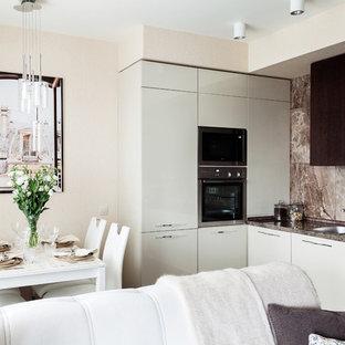 Пример оригинального дизайна: маленькая кухня-гостиная в современном стиле с накладной раковиной, плоскими фасадами, коричневым фартуком, фартуком из каменной плитки, техникой из нержавеющей стали и белыми фасадами без острова