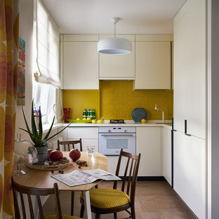 This is an example of a small eclectic l-shaped eat-in kitchen in Yekaterinburg with an undermount sink, flat-panel cabinets, solid surface benchtops, yellow splashback, mosaic tile splashback, white appliances, porcelain floors, brown floor, no island, beige cabinets and beige benchtop.