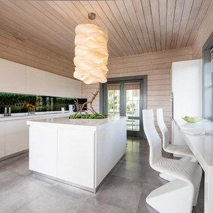 Выдающиеся фото от архитекторов и дизайнеров интерьера: параллельная кухня в современном стиле с обеденным столом, плоскими фасадами, белыми фасадами, фартуком цвета металлик и островом