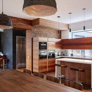 Пример оригинального дизайна: большая кухня в современном стиле с фартуком с окном, обеденным столом, плоскими фасадами, фасадами цвета дерева среднего тона, черной техникой, островом, коричневым полом и белой столешницей