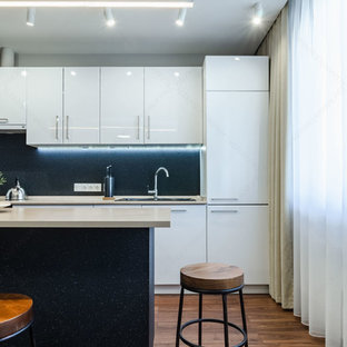 This is an example of a mid-sized contemporary galley separate kitchen in Other with a single-bowl sink, flat-panel cabinets, white cabinets, laminate benchtops, black appliances, laminate floors, with island, brown floor and beige benchtop.
