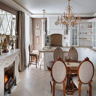Новые идеи обустройства дома: кухня - столовая в классическом стиле с белыми фасадами, техникой под мебельный фасад, светлым паркетным полом и полуостровом