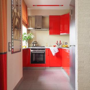 На фото: п-образная кухня в современном стиле с плоскими фасадами, красными фасадами, техникой из нержавеющей стали, серым полом, бежевым фартуком и фартуком из стекла без острова с