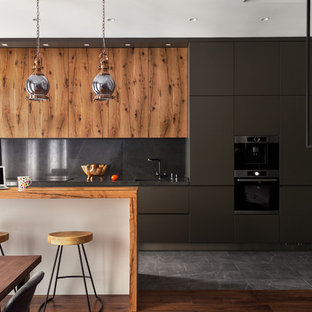 На фото: линейная кухня-гостиная в современном стиле с плоскими фасадами, черным фартуком, техникой из нержавеющей стали, островом, серым полом, серыми фасадами и деревянной столешницей с