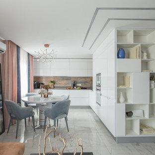 На фото: угловые кухни-гостиные в современном стиле с плоскими фасадами, белыми фасадами, коричневым фартуком, белой техникой и белым полом без острова