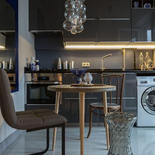 Неиссякаемый источник вдохновения для домашнего уюта: маленькая линейная кухня в современном стиле с плоскими фасадами, серыми фасадами, серым фартуком, техникой из нержавеющей стали, белым полом и обеденным столом без острова