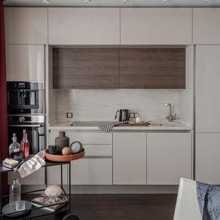 Стильный дизайн: маленькая прямая кухня-гостиная в современном стиле с монолитной раковиной, плоскими фасадами, бежевыми фасадами, бежевым фартуком, коричневым полом, бежевой столешницей, фартуком из каменной плиты, черной техникой и темным паркетным полом без острова - последний тренд