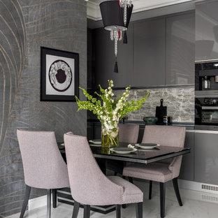 Источник вдохновения для домашнего уюта: угловая кухня-гостиная в современном стиле с плоскими фасадами, серыми фасадами, бежевым фартуком, черной техникой и белым полом без острова