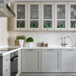 На фото: угловая кухня среднего размера в современном стиле с обеденным столом, врезной раковиной, фасадами с утопленной филенкой, бежевым фартуком, техникой из нержавеющей стали, серым полом и серыми фасадами с