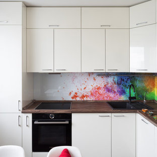 This is an example of a mid-sized contemporary l-shaped separate kitchen in Moscow with flat-panel cabinets, white cabinets, laminate benchtops, multi-coloured splashback, glass sheet splashback, black appliances, vinyl floors, no island, brown floor and a drop-in sink.
