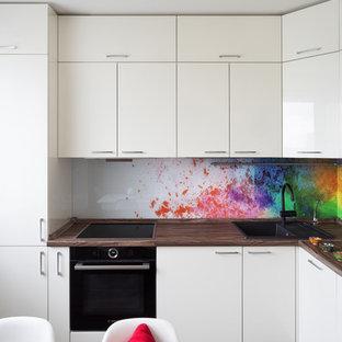 Idéer för ett avskilt, mellanstort modernt l-kök, med släta luckor, vita skåp, laminatbänkskiva, flerfärgad stänkskydd, glaspanel som stänkskydd, svarta vitvaror, vinylgolv, brunt golv och en nedsänkt diskho