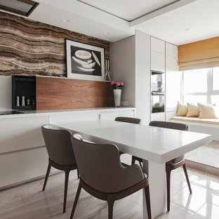 Photo of a large contemporary u-shaped eat-in kitchen in Other with an undermount sink, flat-panel cabinets, beige cabinets, solid surface benchtops, white splashback, timber splashback, black appliances, porcelain floors, a peninsula, beige floor and white benchtop.
