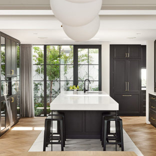 This is an example of a transitional u-shaped eat-in kitchen with black cabinets, light hardwood floors, white benchtop, an undermount sink, shaker cabinets, panelled appliances, with island and brown floor.