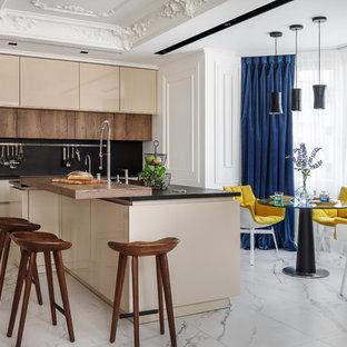 Пример оригинального дизайна: кухня в стиле современная классика с обеденным столом, плоскими фасадами, бежевыми фасадами, черным фартуком, островом, белым полом и черной столешницей