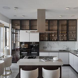 На фото: угловая кухня в современном стиле с накладной раковиной, стеклянными фасадами, белым фартуком, черной техникой, островом и белым полом