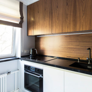 Пример оригинального дизайна: маленькая угловая кухня в современном стиле с обеденным столом, одинарной раковиной, плоскими фасадами, белыми фасадами, столешницей из кварцевого агломерата, коричневым фартуком, фартуком из дерева, черной техникой, полом из керамогранита, белым полом и черной столешницей без острова