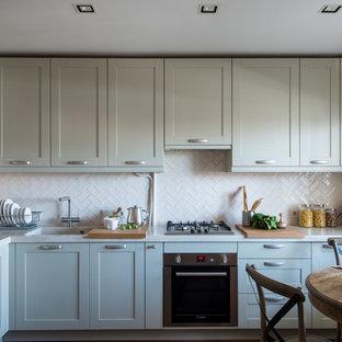 Идея дизайна: отдельная, угловая кухня в современном стиле с монолитной раковиной, фасадами в стиле шейкер, серыми фасадами, белым фартуком, техникой из нержавеющей стали и белой столешницей