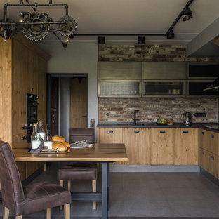Неиссякаемый источник вдохновения для домашнего уюта: угловая кухня в стиле лофт с врезной раковиной, плоскими фасадами, светлыми деревянными фасадами, коричневым фартуком, фартуком из кирпича, черной техникой, серым полом, черной столешницей и обеденным столом без острова
