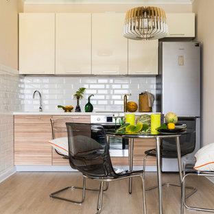Идея дизайна: маленькая угловая кухня в современном стиле с обеденным столом, плоскими фасадами, бежевыми фасадами, белым фартуком, фартуком из плитки кабанчик, техникой из нержавеющей стали, светлым паркетным полом, бежевым полом и белой столешницей без острова