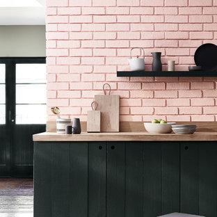Ejemplo de cocina bohemia con armarios con paneles lisos, puertas de armario negras, encimera de madera, salpicadero rosa, salpicadero de ladrillos, suelo de madera oscura y suelo marrón