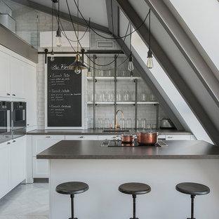 На фото: угловые кухни в современном стиле с накладной раковиной, фасадами с утопленной филенкой, белыми фасадами, белым фартуком, полуостровом, белым полом и серой столешницей