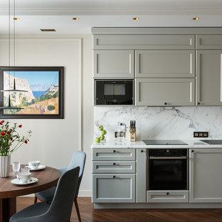 Пример оригинального дизайна: угловая кухня-гостиная в стиле современная классика с накладной раковиной, фасадами с утопленной филенкой, серыми фасадами, белым фартуком, черной техникой, темным паркетным полом, коричневым полом и белой столешницей без острова