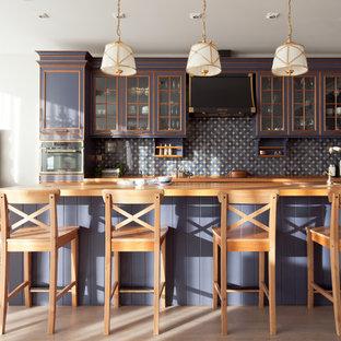 Свежая идея для дизайна: параллельная кухня-гостиная в классическом стиле с столешницей из дерева, синим фартуком, черной техникой, светлым паркетным полом, островом, стеклянными фасадами, синими фасадами, фартуком из керамогранитной плитки и бежевым полом - отличное фото интерьера