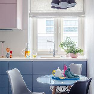 Minimalistisk inredning av ett avskilt, litet l-kök, med en integrerad diskho, släta luckor, blå skåp, bänkskiva i koppar, stänkskydd i porslinskakel, mörkt trägolv, grått golv och vitt stänkskydd