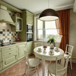 Klassisk inredning av ett kök och matrum, med luckor med upphöjd panel, gröna skåp, flerfärgad stänkskydd, svarta vitvaror och klinkergolv i terrakotta