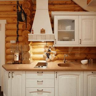 Новые идеи обустройства дома: линейная кухня в стиле кантри с белыми фасадами, фартуком из стекла, монолитной раковиной, коричневым фартуком и обеденным столом без острова