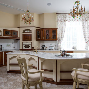 На фото: кухня в классическом стиле с врезной раковиной, стеклянными фасадами, темными деревянными фасадами, разноцветным фартуком, цветной техникой, островом, бежевым полом и разноцветной столешницей с