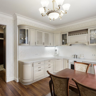 This is an example of a mid-sized traditional l-shaped eat-in kitchen in Other with an undermount sink, glass-front cabinets, beige cabinets, solid surface benchtops, white splashback, ceramic splashback, white appliances, laminate floors, no island, brown floor and white benchtop.