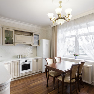 Mid-sized traditional l-shaped eat-in kitchen in Other with an undermount sink, glass-front cabinets, beige cabinets, solid surface benchtops, white splashback, ceramic splashback, white appliances, laminate floors, no island, brown floor and white benchtop.