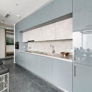 Пример оригинального дизайна: большая, серо-белая прямая кухня в современном стиле с монолитной раковиной, плоскими фасадами, серыми фасадами, белым фартуком, техникой под мебельный фасад, серым полом и белой столешницей без острова