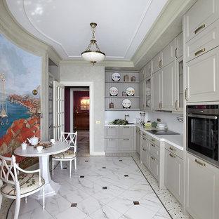 Выдающиеся фото от архитекторов и дизайнеров интерьера: отдельная, угловая кухня в классическом стиле с серыми фасадами, белым фартуком, техникой из нержавеющей стали и мраморным полом без острова