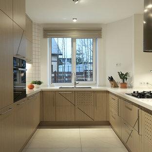 На фото: п-образная кухня-гостиная в скандинавском стиле с врезной раковиной, плоскими фасадами, светлыми деревянными фасадами, белым фартуком, черной техникой, полуостровом и белым полом с