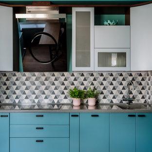 Пример оригинального дизайна: угловая кухня-гостиная среднего размера в современном стиле с монолитной раковиной, плоскими фасадами, столешницей из кварцевого агломерата, серым фартуком, паркетным полом среднего тона и серой столешницей