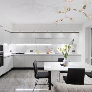 На фото: угловая кухня-гостиная в современном стиле с плоскими фасадами, белыми фасадами, техникой из нержавеющей стали, серым полом и белой столешницей с